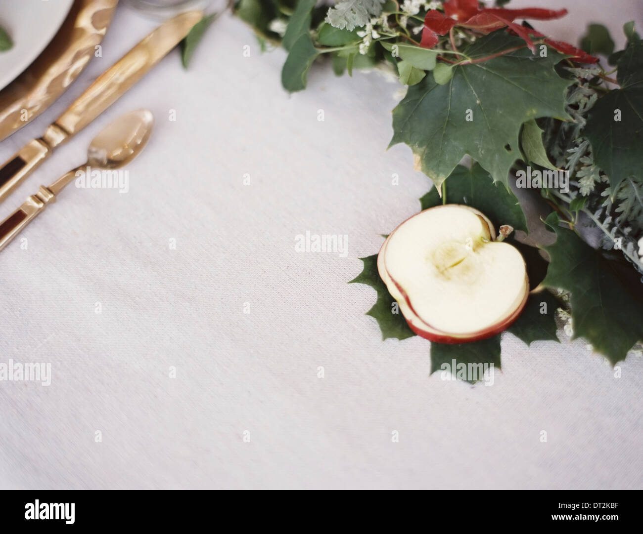 A table top white cloth A place setting with cutlery and plate An apple cut in half and green foliage table decoration - Stock Image