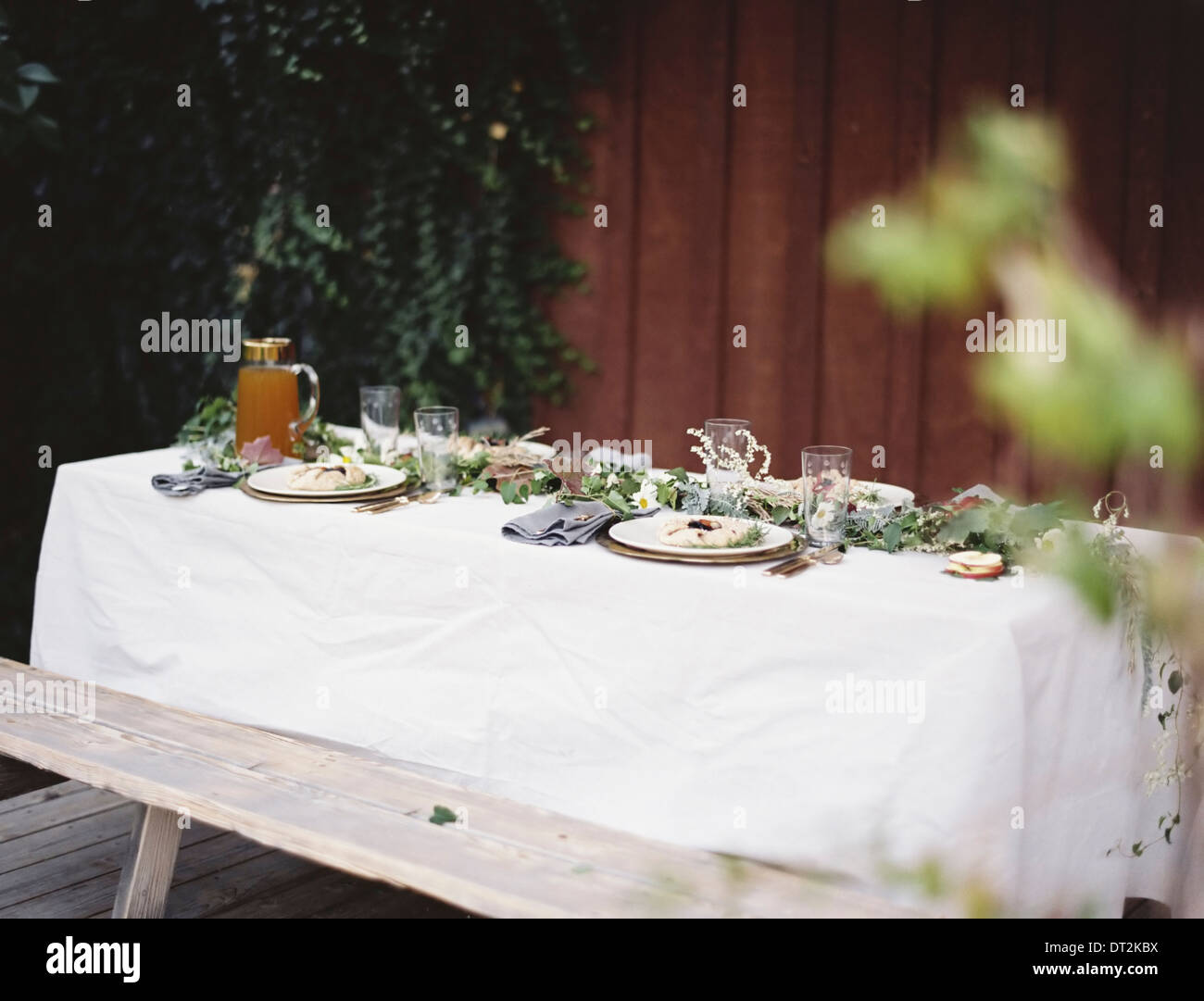 A table laid for a special meal Place settings with plates and cutlery Glasses A white table cloth and bench seat Plates of food - Stock Image