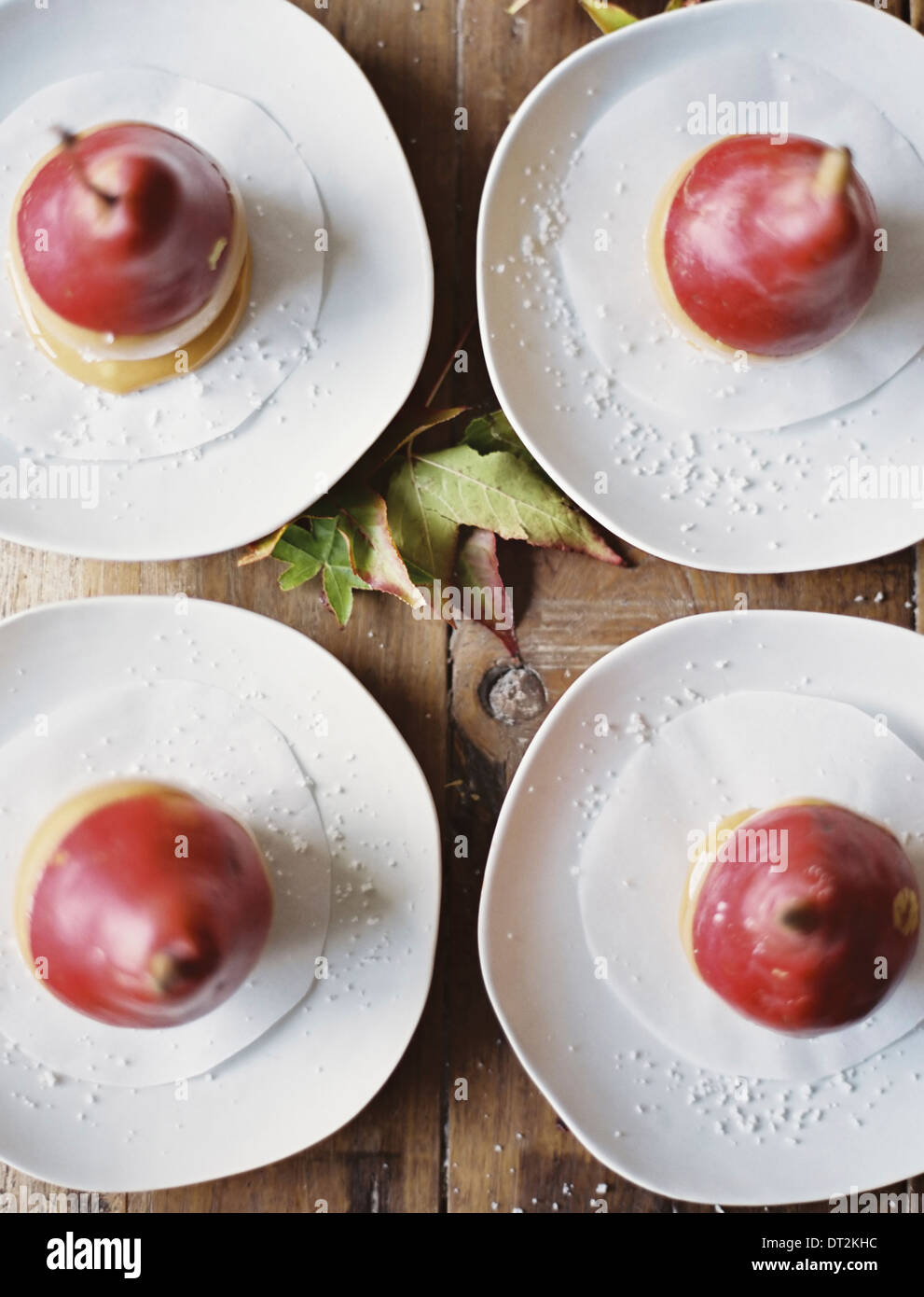 Tabletop viewed from above Four plates with dessert Pears dipped in sauce - Stock Image