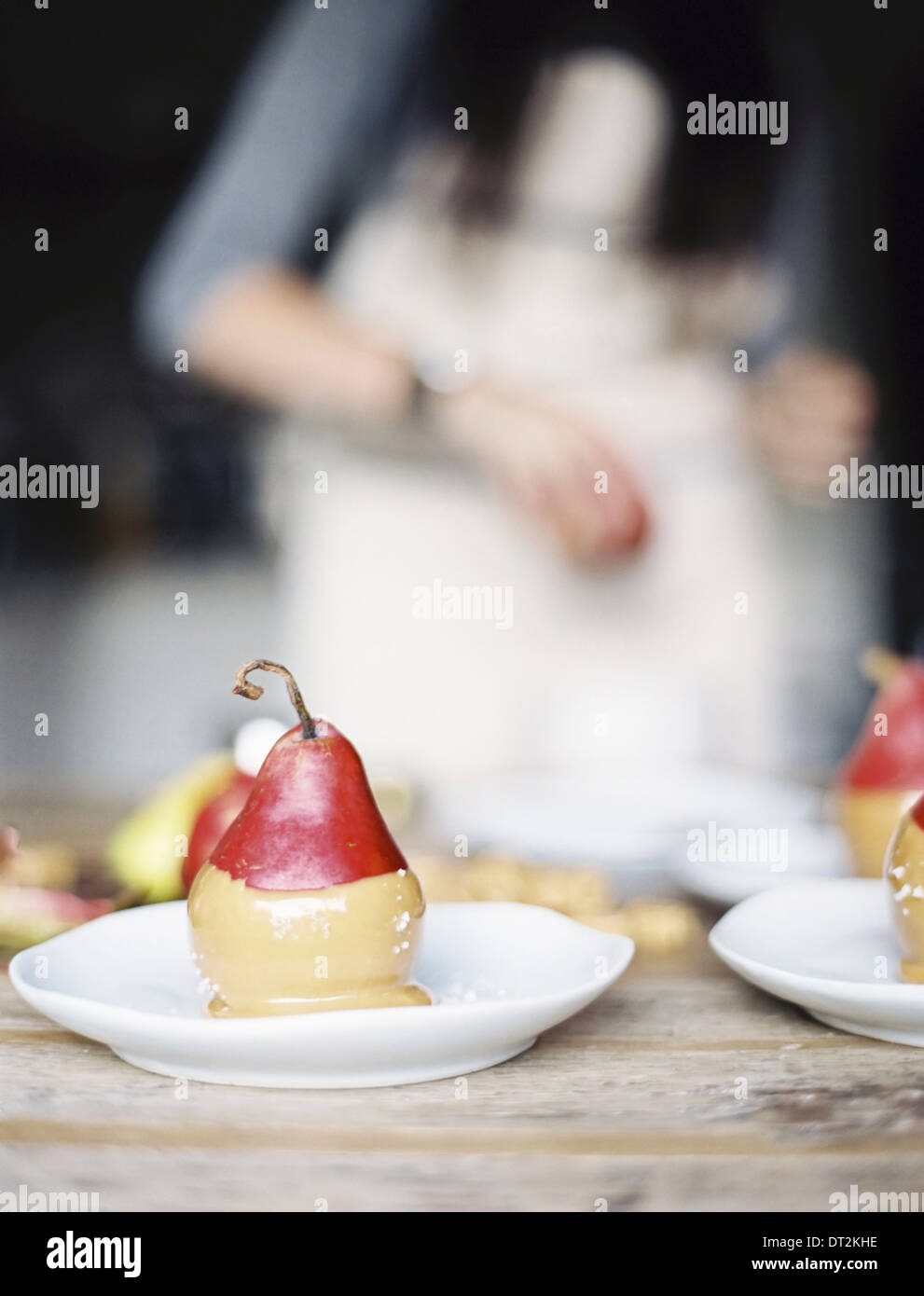 A woman in a domestic kitchen Fresh organic pears dipped into a sauce for dessert laid out on plates - Stock Image