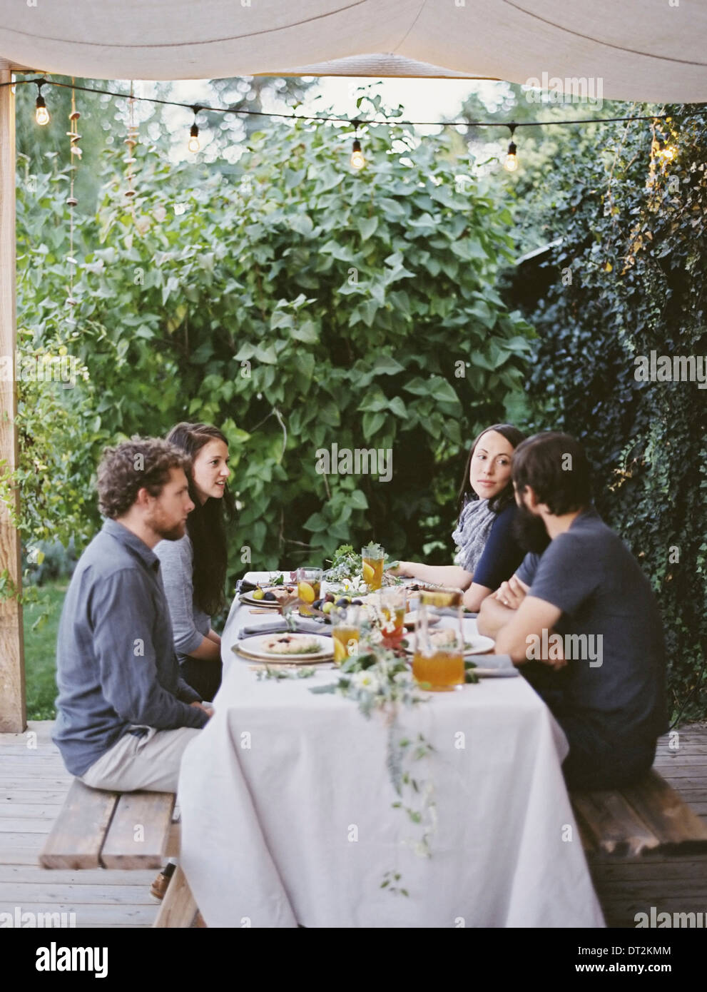 Four people seated at a table in the garden Place settings and decorations on a white tablecloth Two men and two - Stock Image