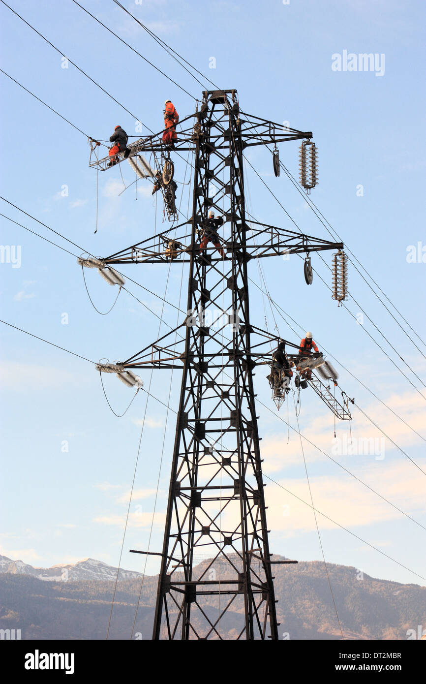 Workers at electricity pylons in Italy. Maintenance work of a high-voltage power line. - Stock Image