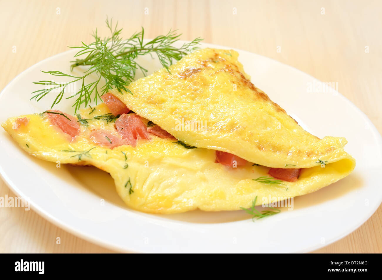 Omelet with tomatoes and herbs on white plate - Stock Image