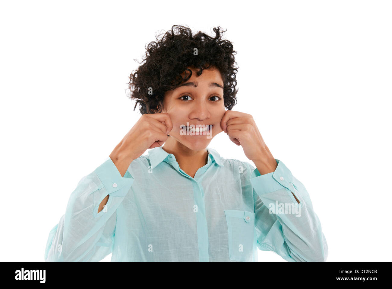 hispanic woman doing facial expression, giving herself a pinch on cheek to smile while looking at camera on white background - Stock Image