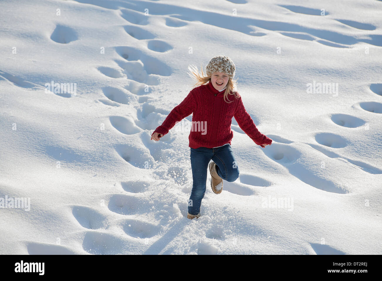 Winter scenery with snow on the ground A young girl running through deep snow making footprint tracks - Stock Image