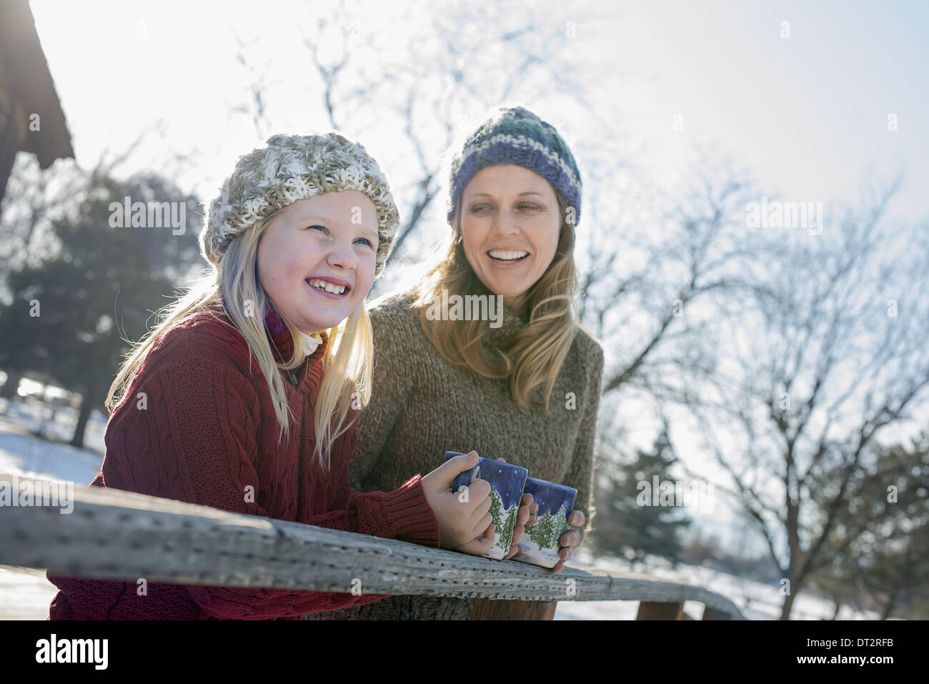 Winter scenery with snow on the ground A child and an adult having a hot drink on a cold day - Stock Image