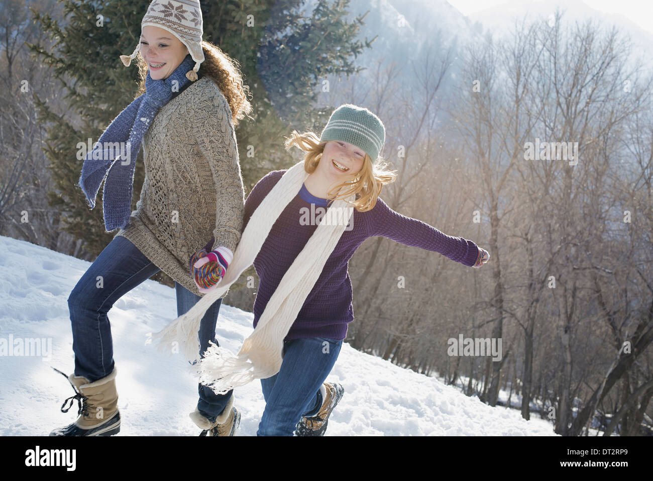 Winter scenery with snow on the ground A woman and a child hand in hand running across the snow Stock Photo