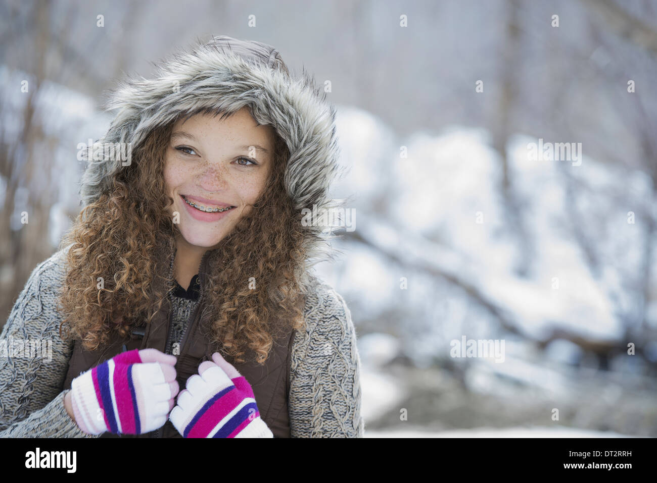 Winter scenery with snow on the ground A young girl in a woolly hat with ski gloves on - Stock Image