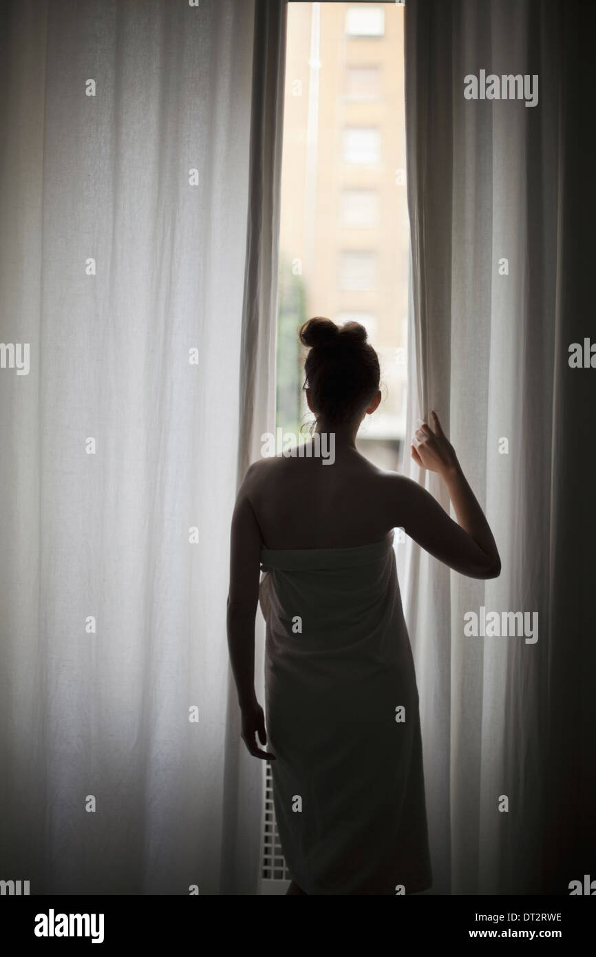 A young woman with her hair up wearing a bath towel looking through long curtains at a window - Stock Image