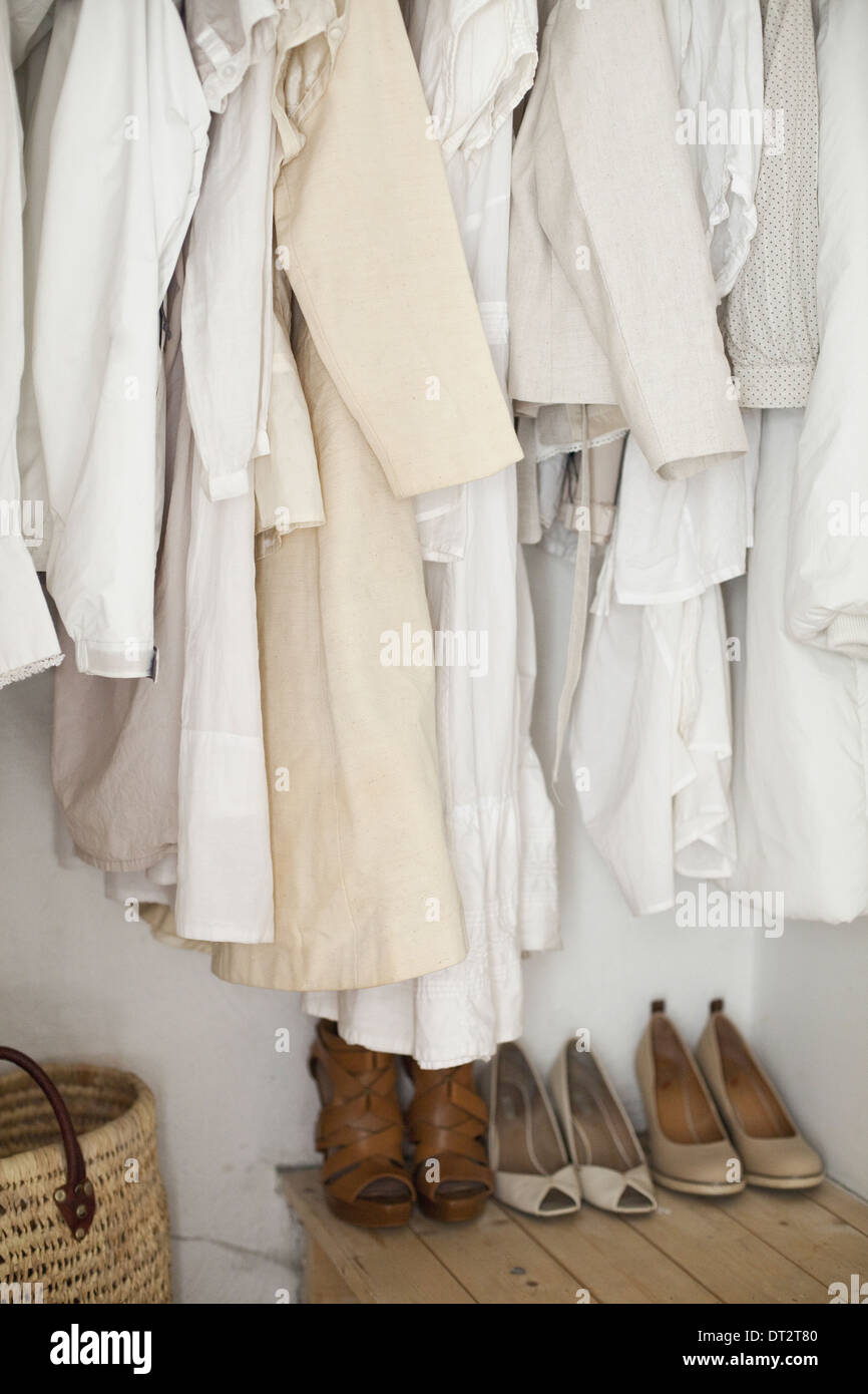 A closet with cream and white clothes jackets shirts and tunics hanging up A row of women's shoes arranged neatly on the floor - Stock Image