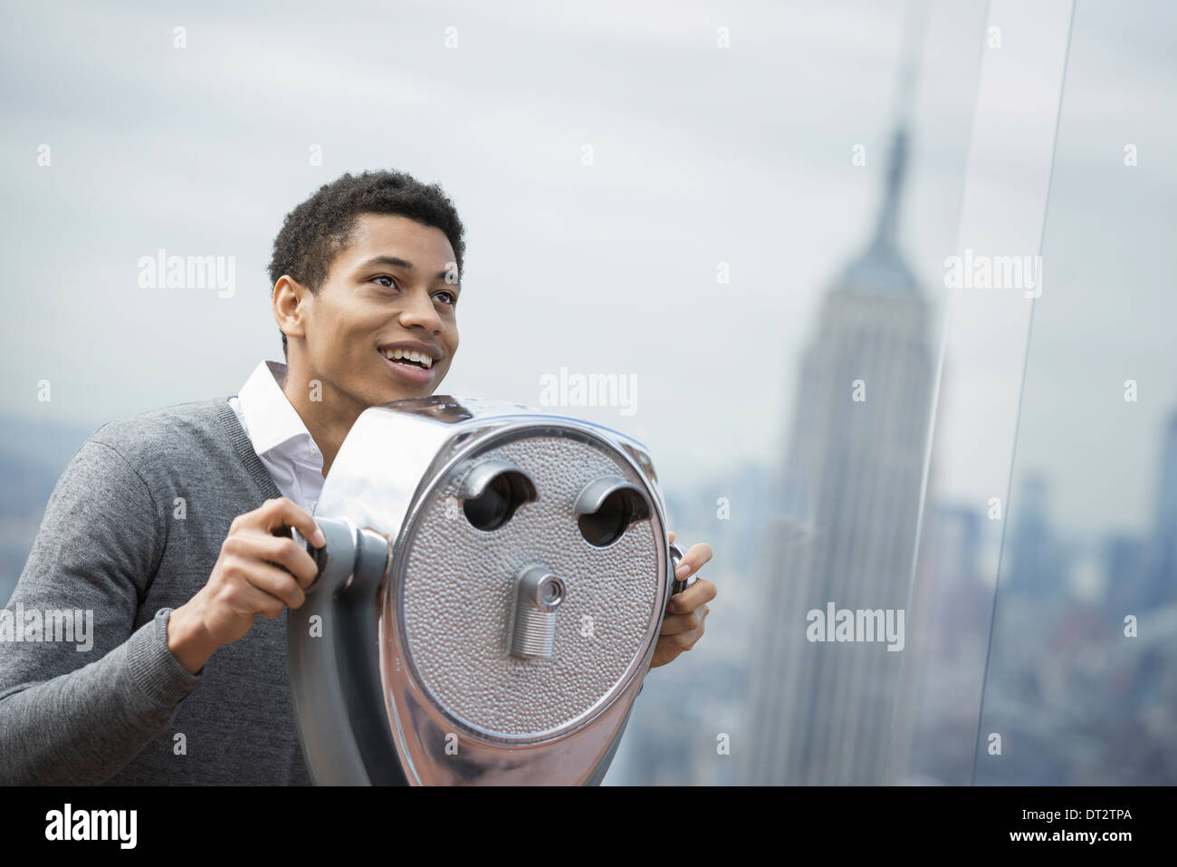View over city young man looking through a telescope over the city - Stock Image