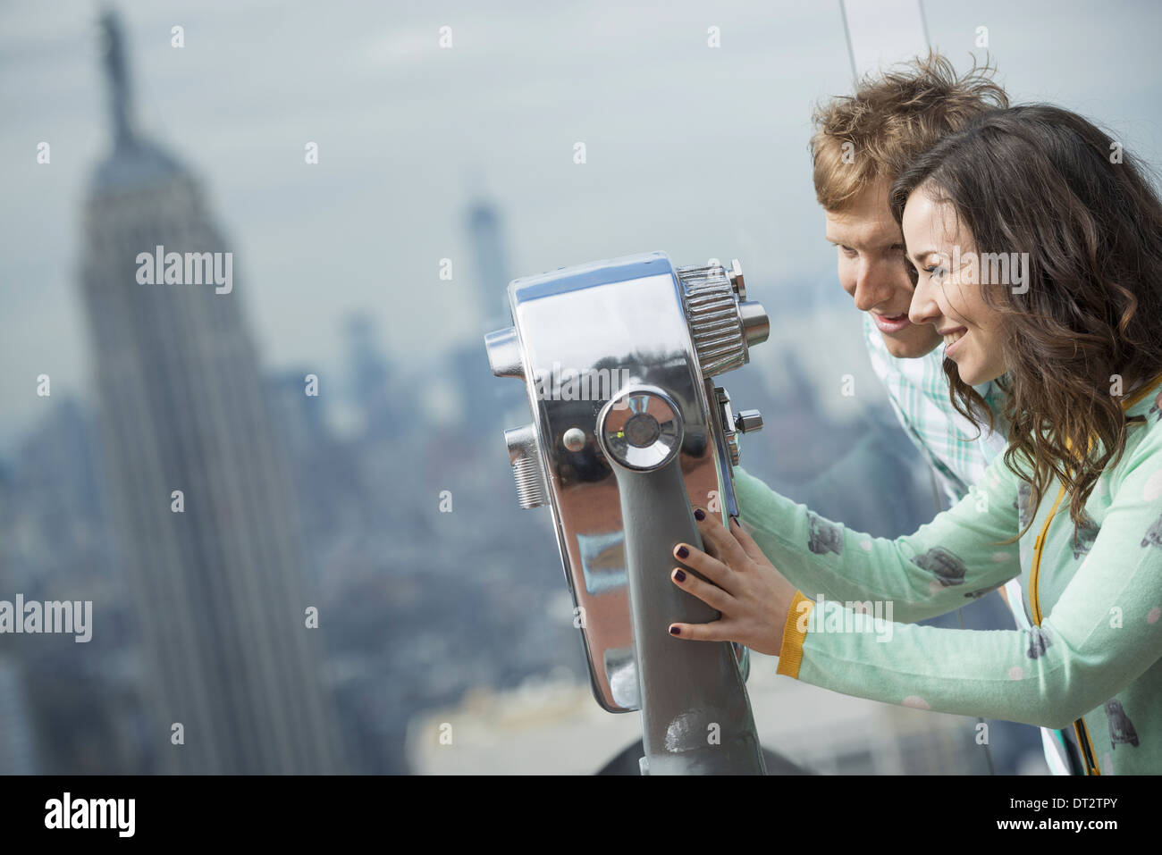 View over cityA young couple looking through the telescope - Stock Image