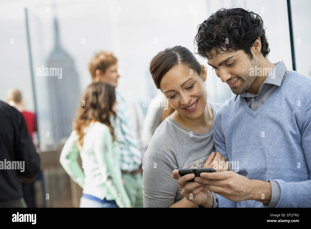 A young couple taking photographs with a mobile phone - Stock Image