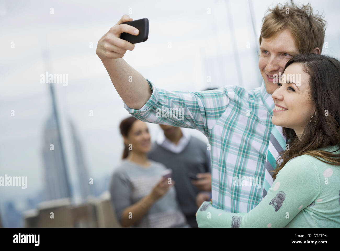 View over cityA man taking a self portrait with a girl - Stock Photo