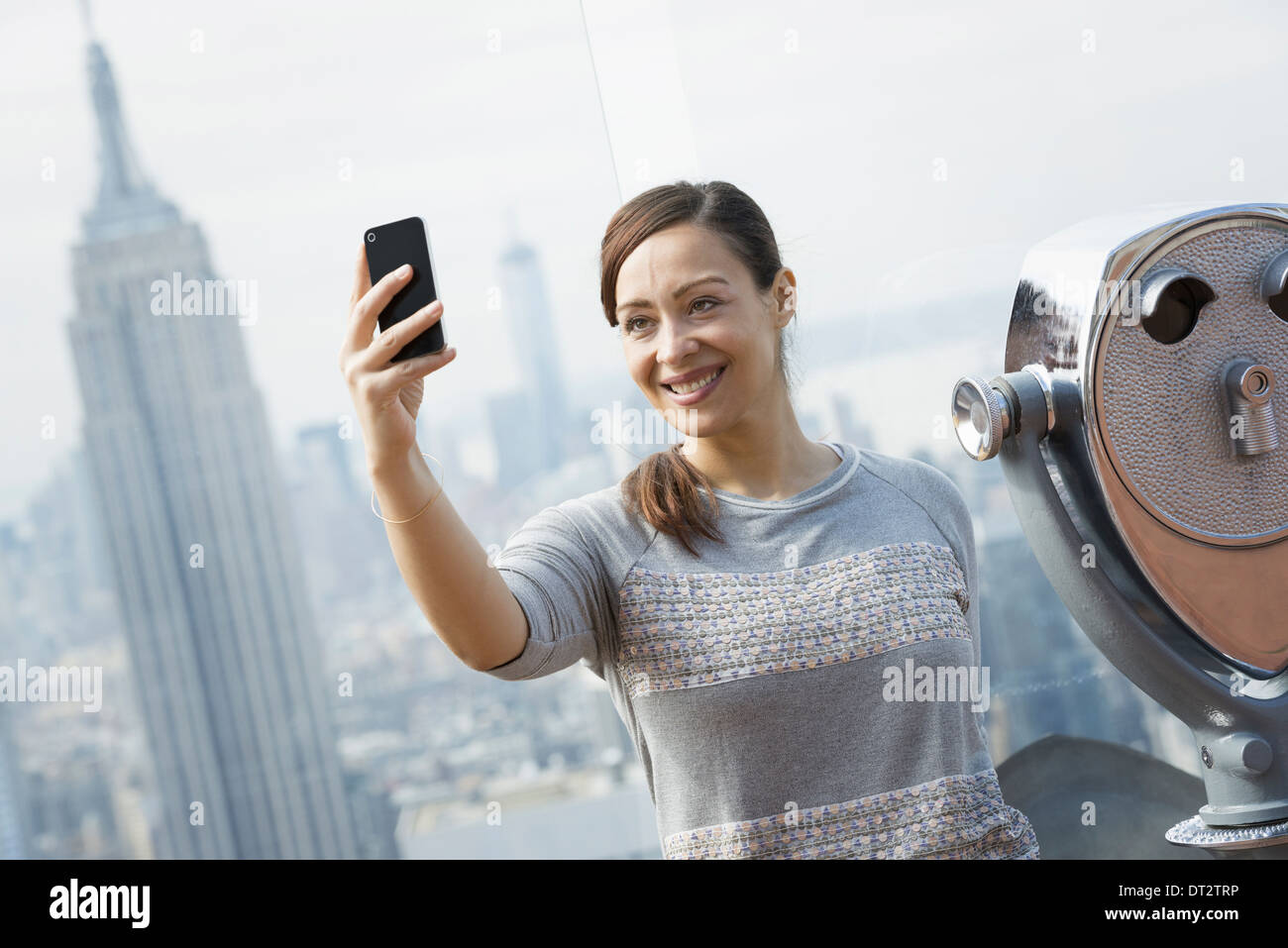 View over cityA woman using her smart phone to photograph the view - Stock Image