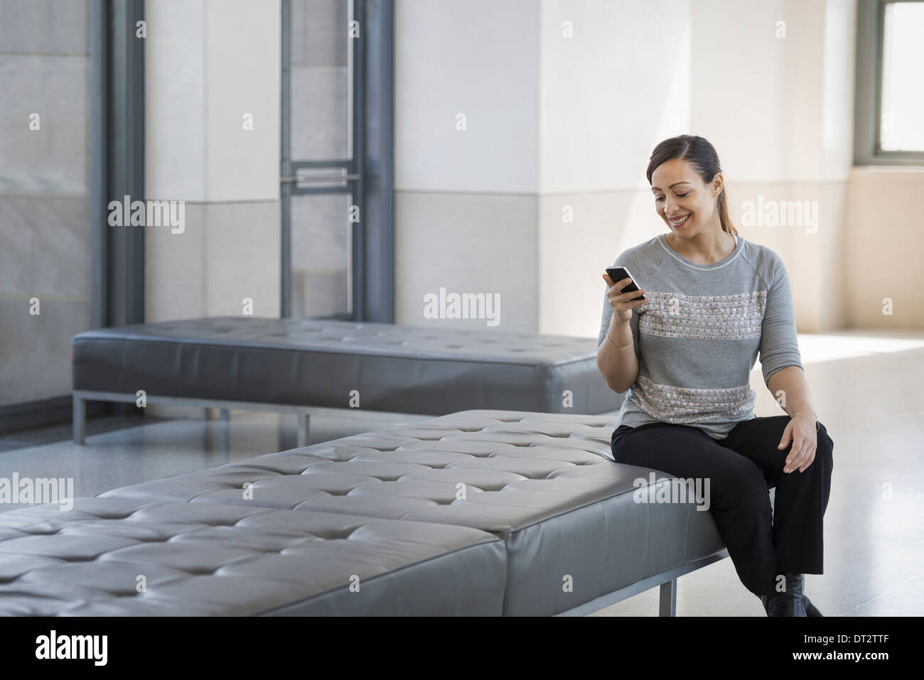 Urban Lifestyle A young woman sitting on a seat in a building using her mobile phone - Stock Image