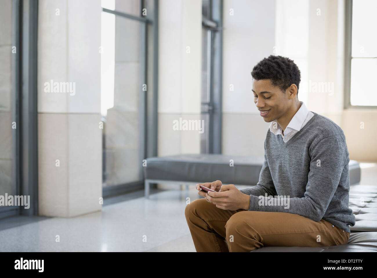 Urban Lifestyle A young man sitting in a lobby on a bench seat Using his mobile phone - Stock Image