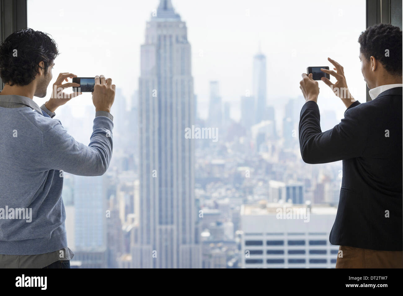 Two young men using their phones to take images of the city from an observation platform overlooking the Empire State Building - Stock Image