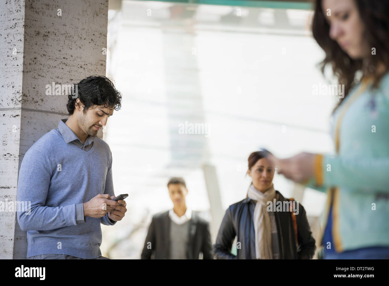 Three people on the sidewalk a man and a young woman using their mobile phones and two people walking on the sidewalk Stock Photo