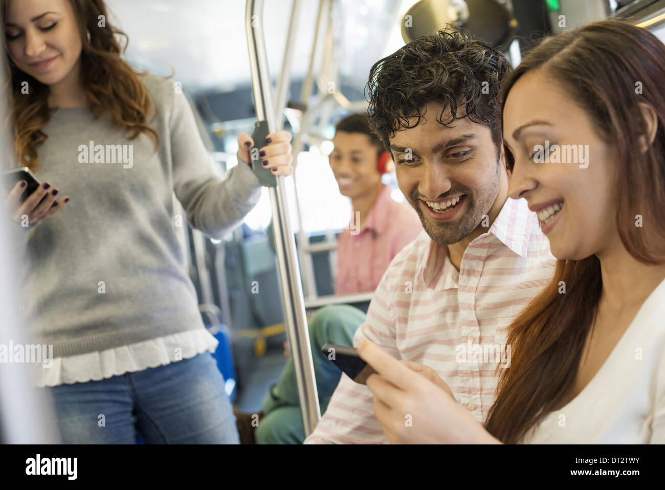 men and women on a city bus in New York city A man wearing headphones and a couple looking at a mobile phone Stock Photo
