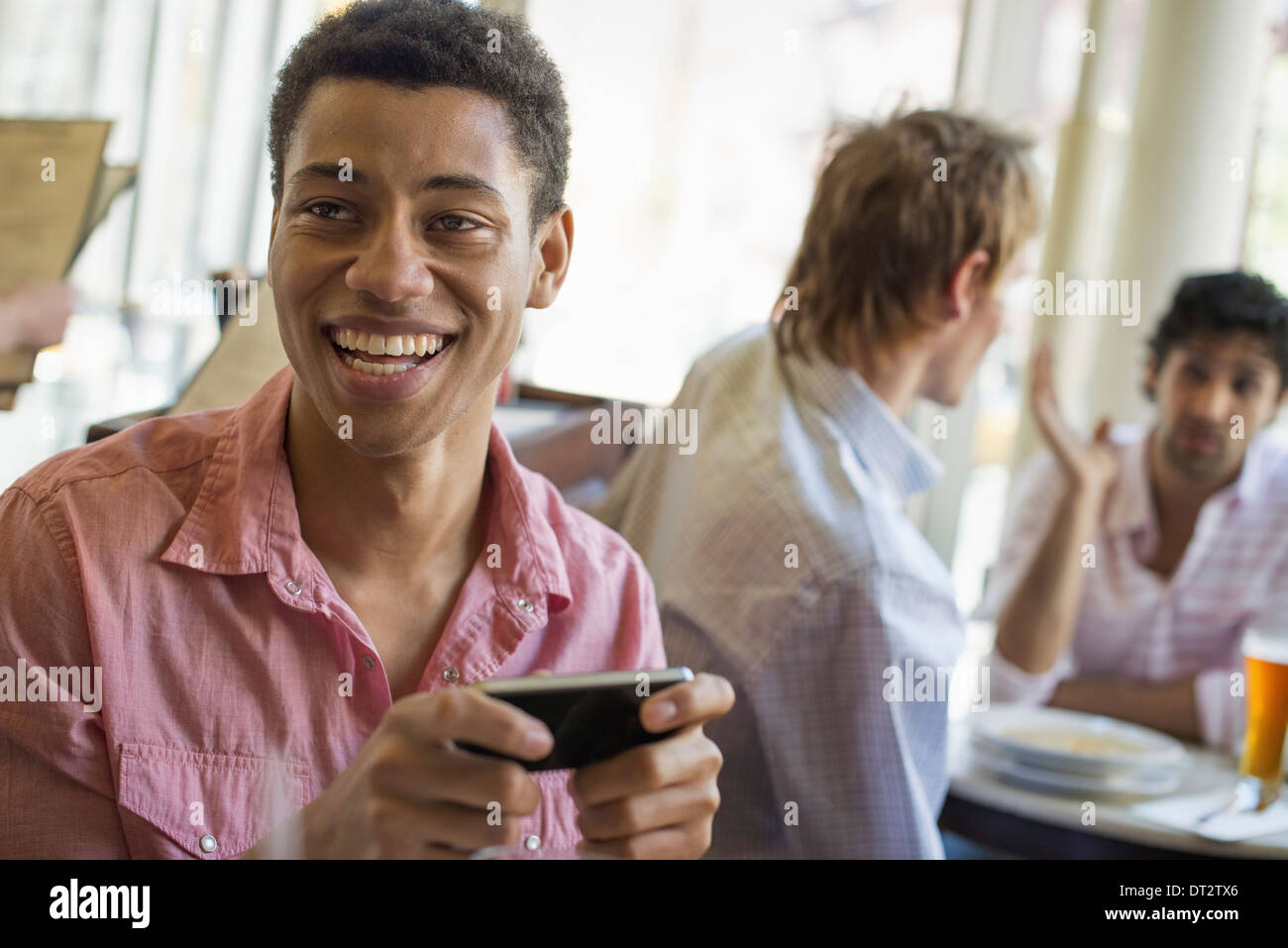 Urban Lifestyle Three young men in a cafe One checking his smart phone Two talking at a table - Stock Image