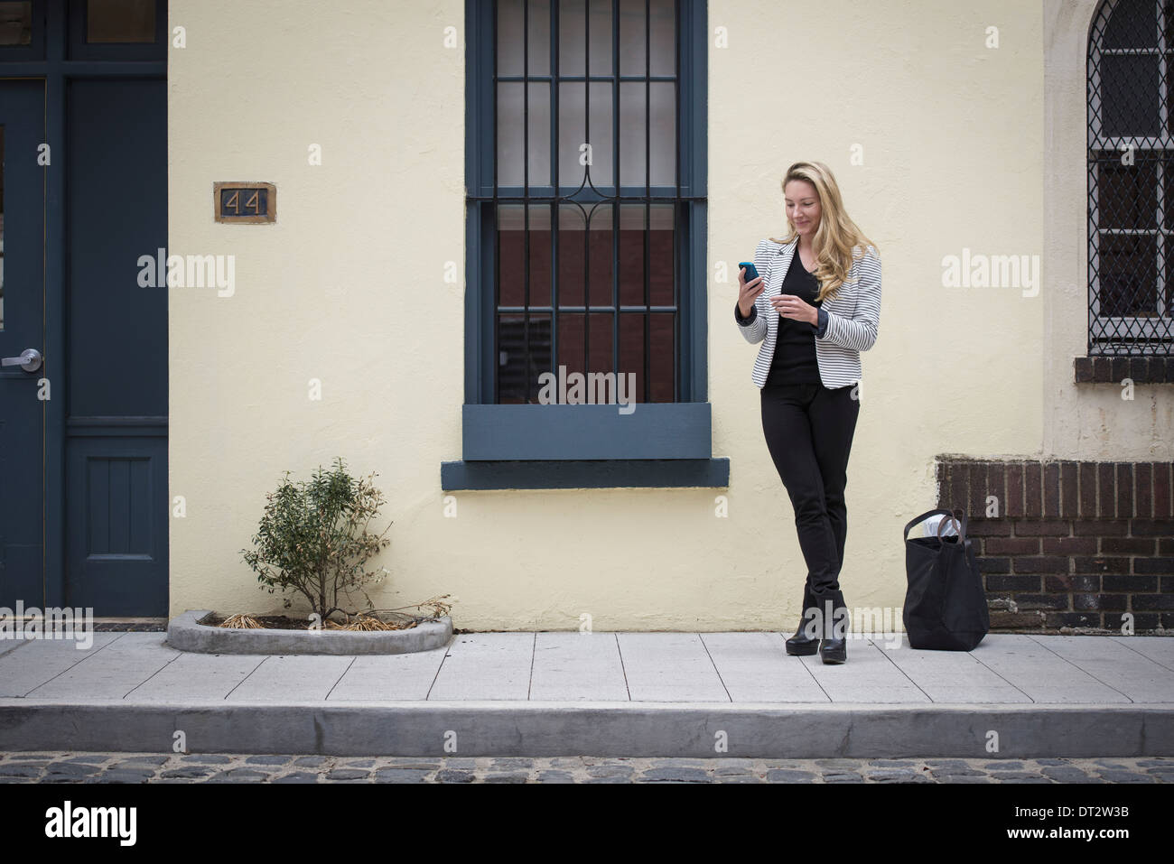 New York city street life Young people in springtime A woman with blonde hair standing on a street sidewalk - Stock Image