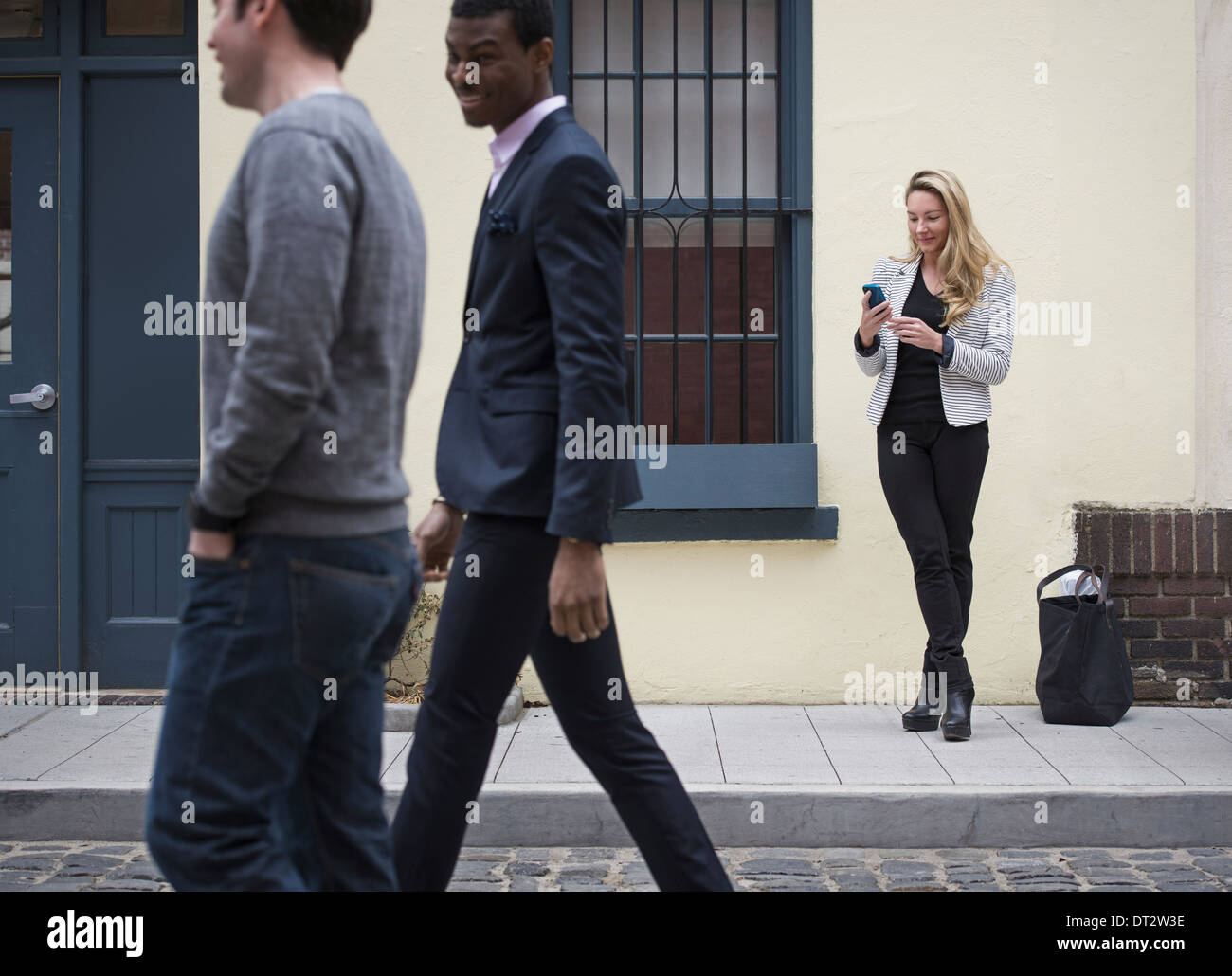 Young people outdoors on the city streets in springtime A woman on her own and two men walking past on the cobbled Stock Photo