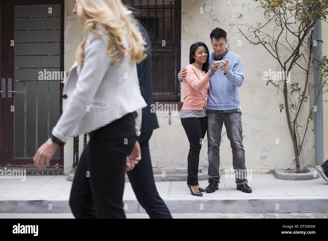 Young people streets in springtime A couple taking images of themselves using a smart phone Two people walking by - Stock Image