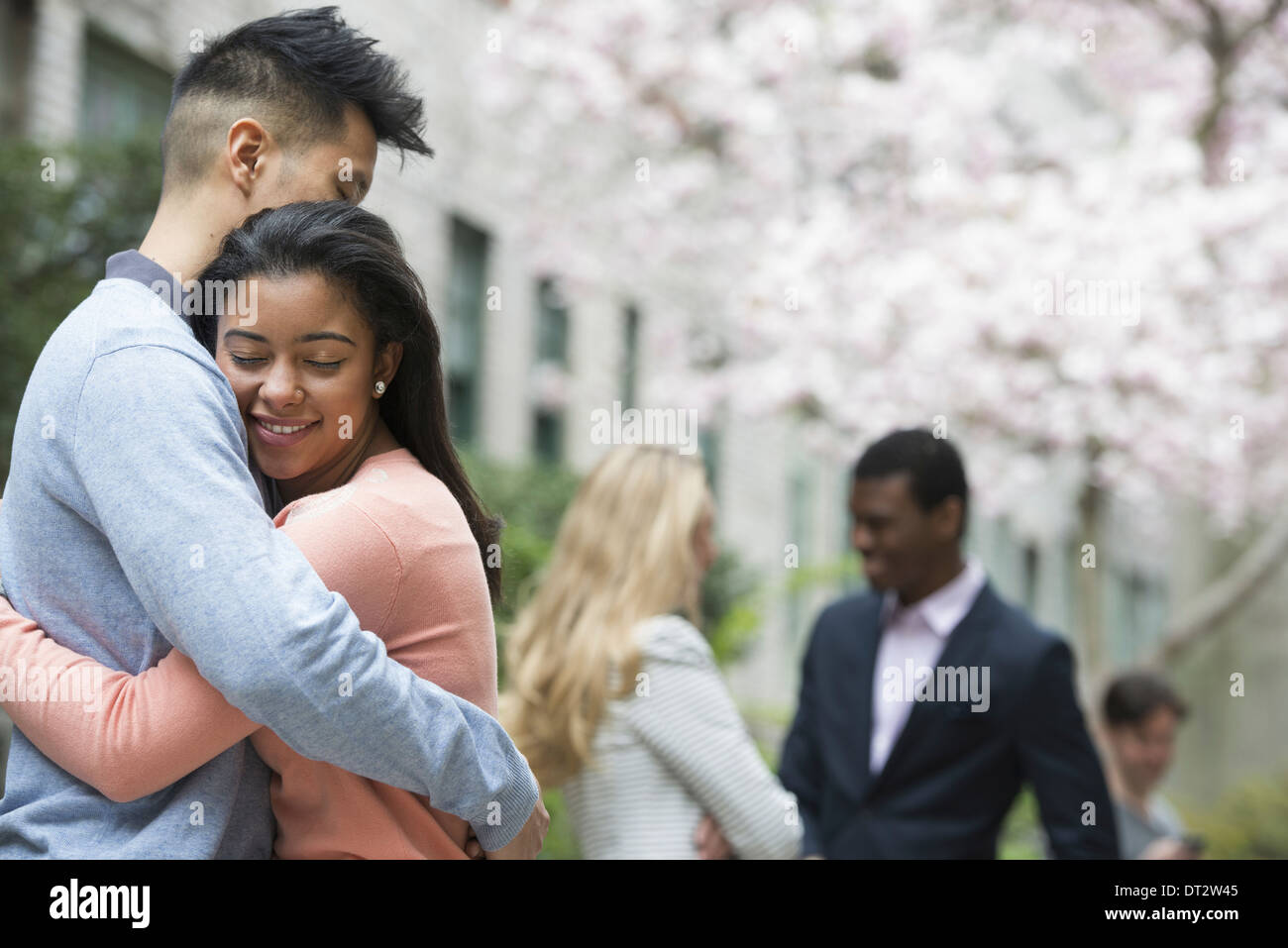 View over cityYoung people outdoors in a city park A couple embracing and two people talking under the trees - Stock Image