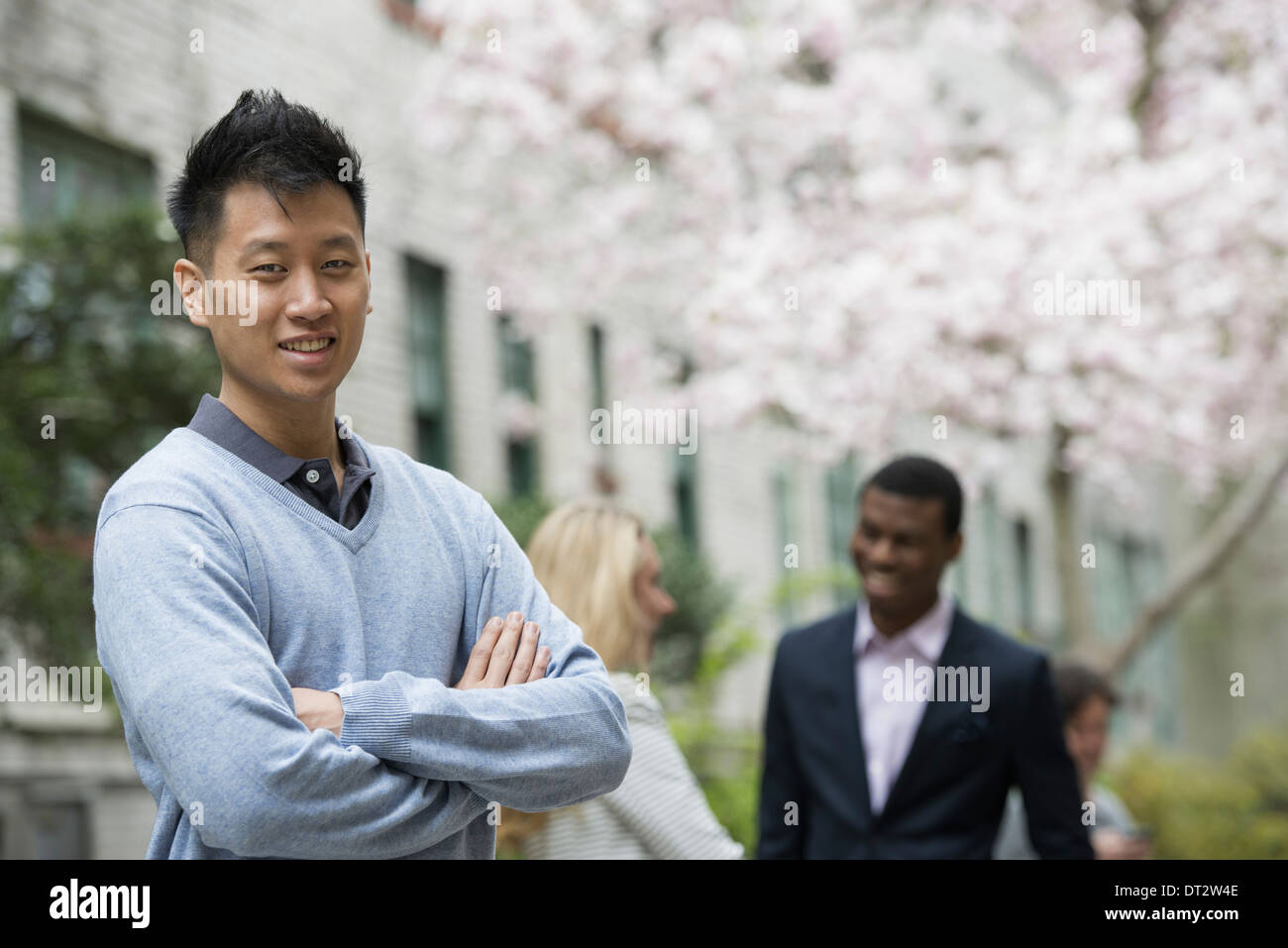 View over cityA man with his arms folded and two people talking in the background under the trees in blossom - Stock Image