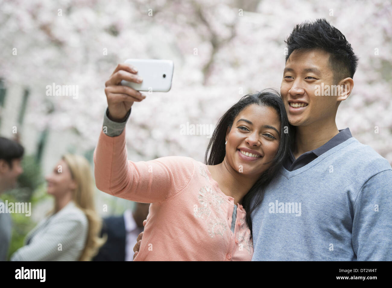 View over cityYoung people outdoors in a city park A couple taking a self portrait or selfy with a smart phone - Stock Image