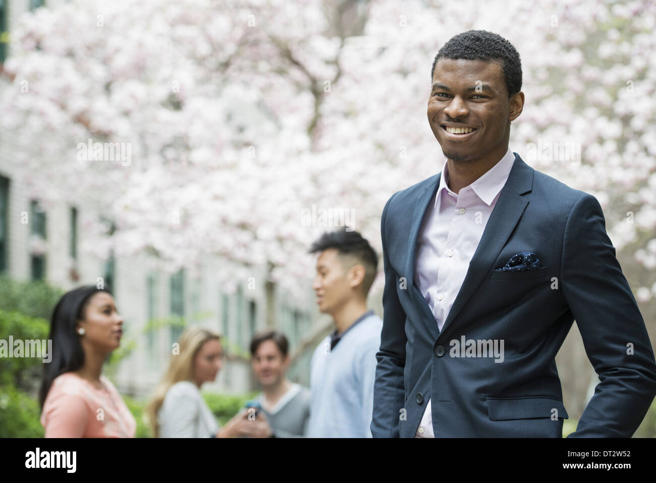Young people outdoors in a city park A man in a suit smiling Four people in the background Using cell phones - Stock Image