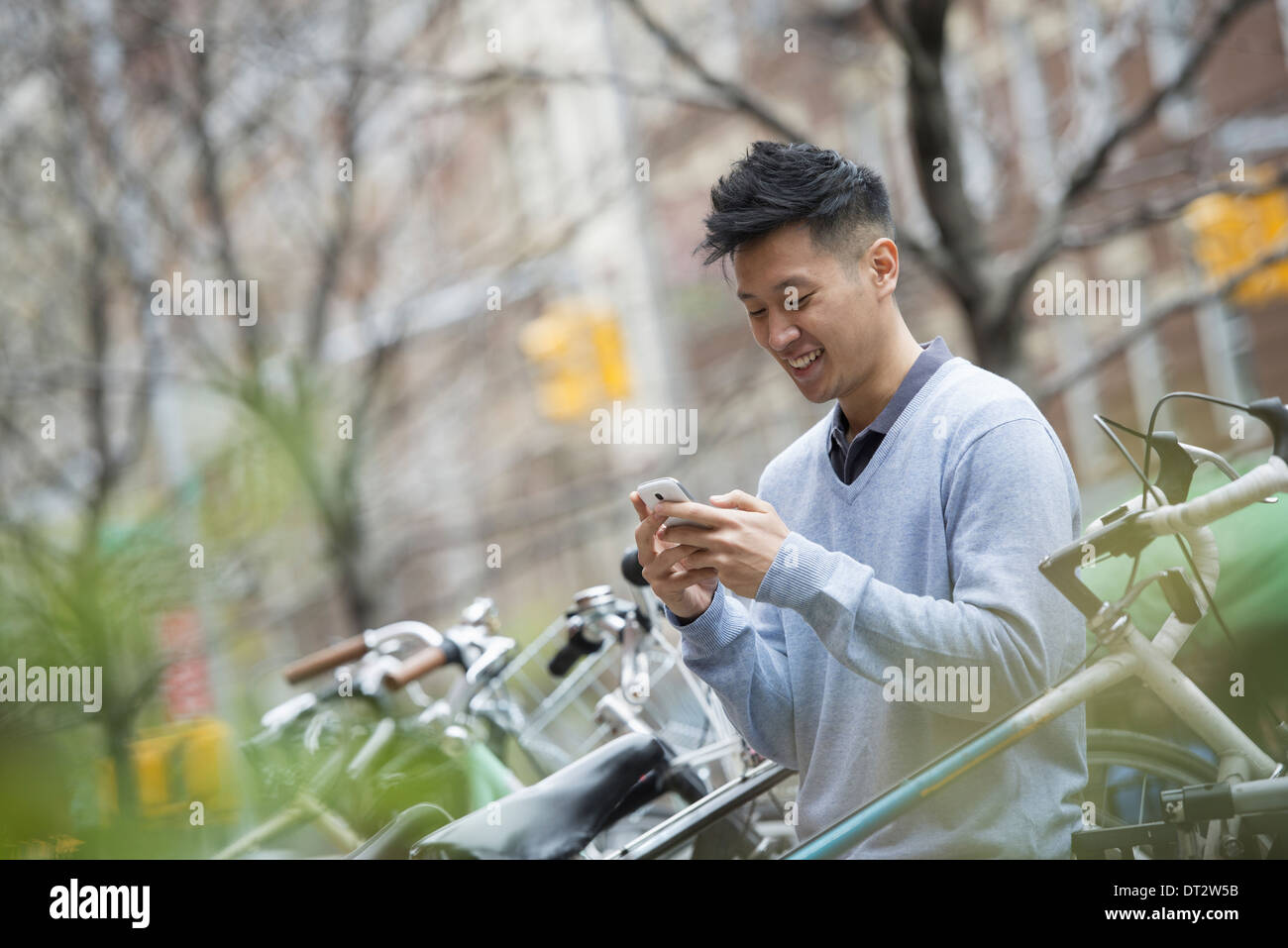 View over cityA man in a blue sweater by a row of parked bicycles Checking his messages on a smart phone - Stock Image