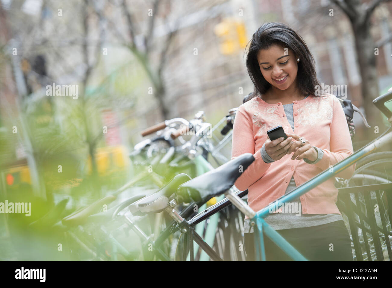 View over cityA young woman in a peach coloured shirt using her smart phone Bicycles parked in a bike rack - Stock Image