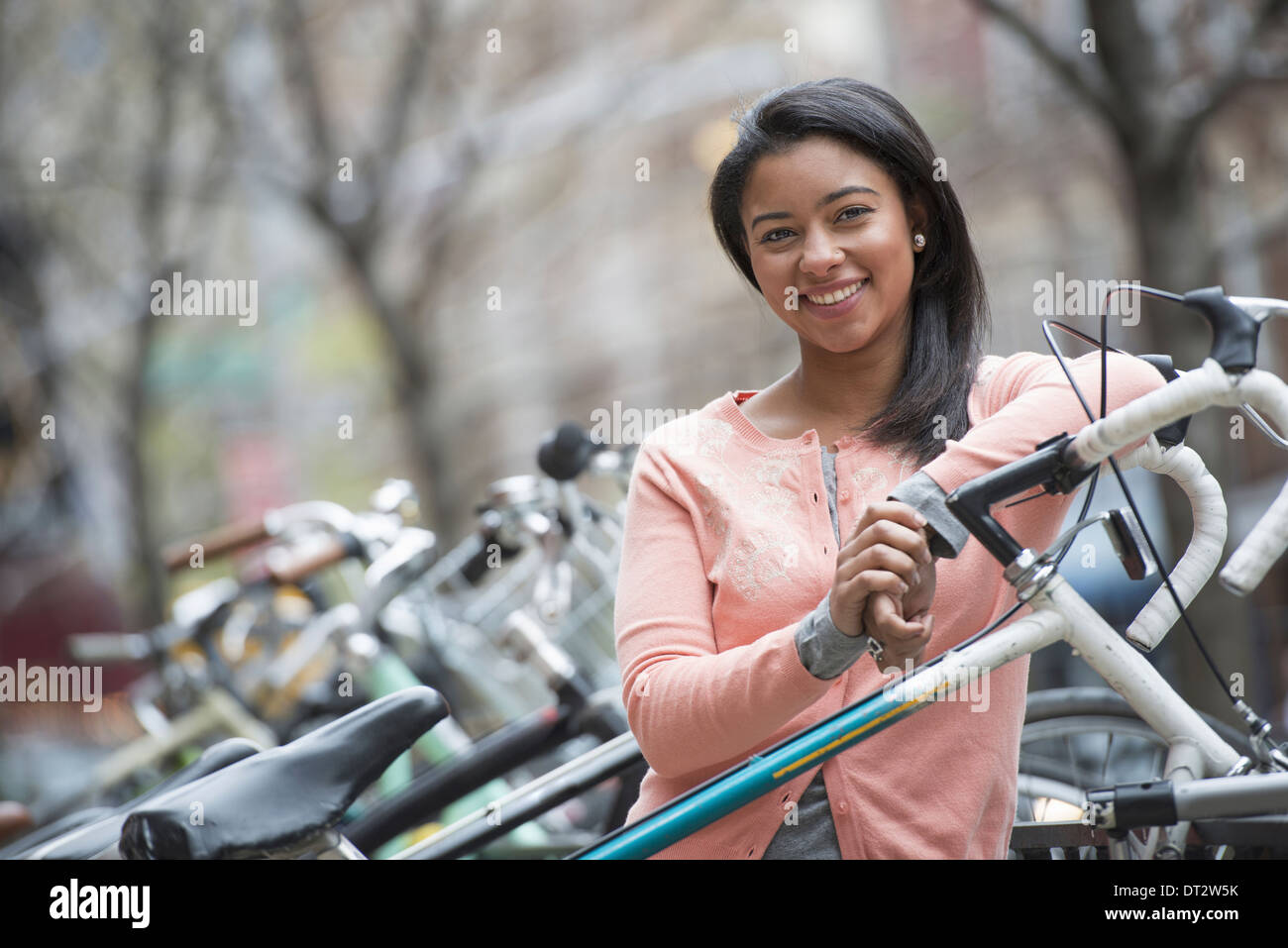 View over cityA young woman with black hair wearing a peach shirt standing beside a rack of parked locked bicycles - Stock Image