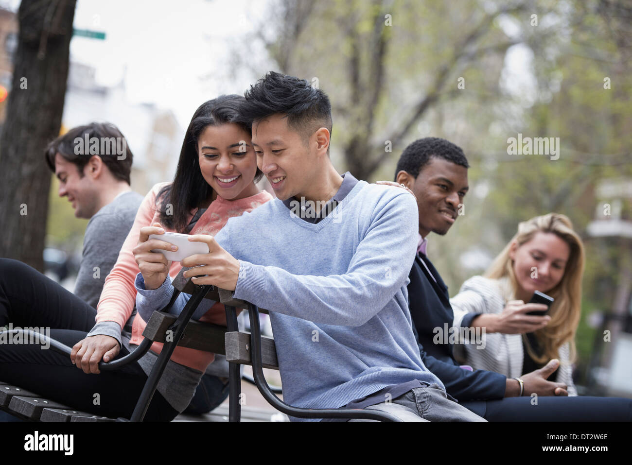 View over city Sitting on a bench A man showing his phone screen to a woman and three other people checking their - Stock Image