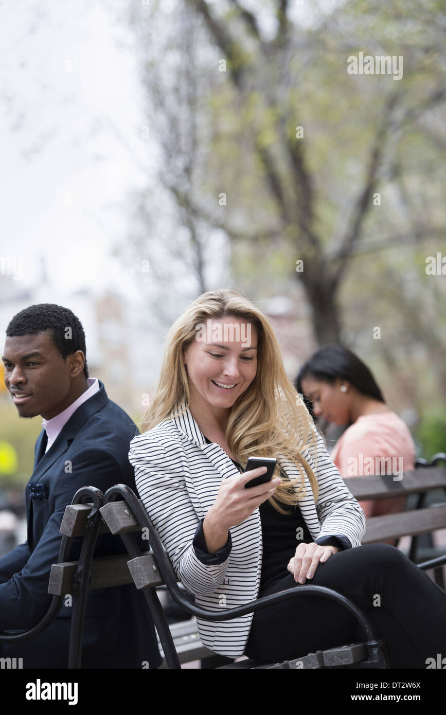 View over cityYoung people outdoors in a city park Three people sitting on a bench Two checking their phones - Stock Image