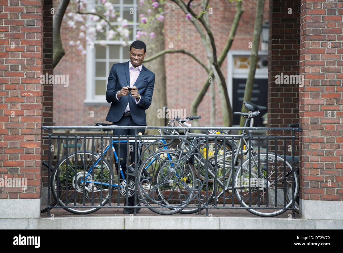 View over cityYoung people in a city park A man in a suit beside a bicycle park on a sidewalk Using his smart phone - Stock Image