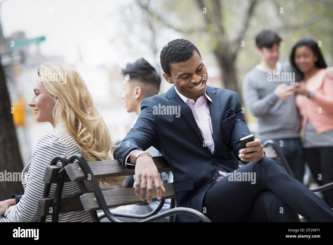 View over city gathered around a park bench Two checking a smart phone for messages - Stock Image