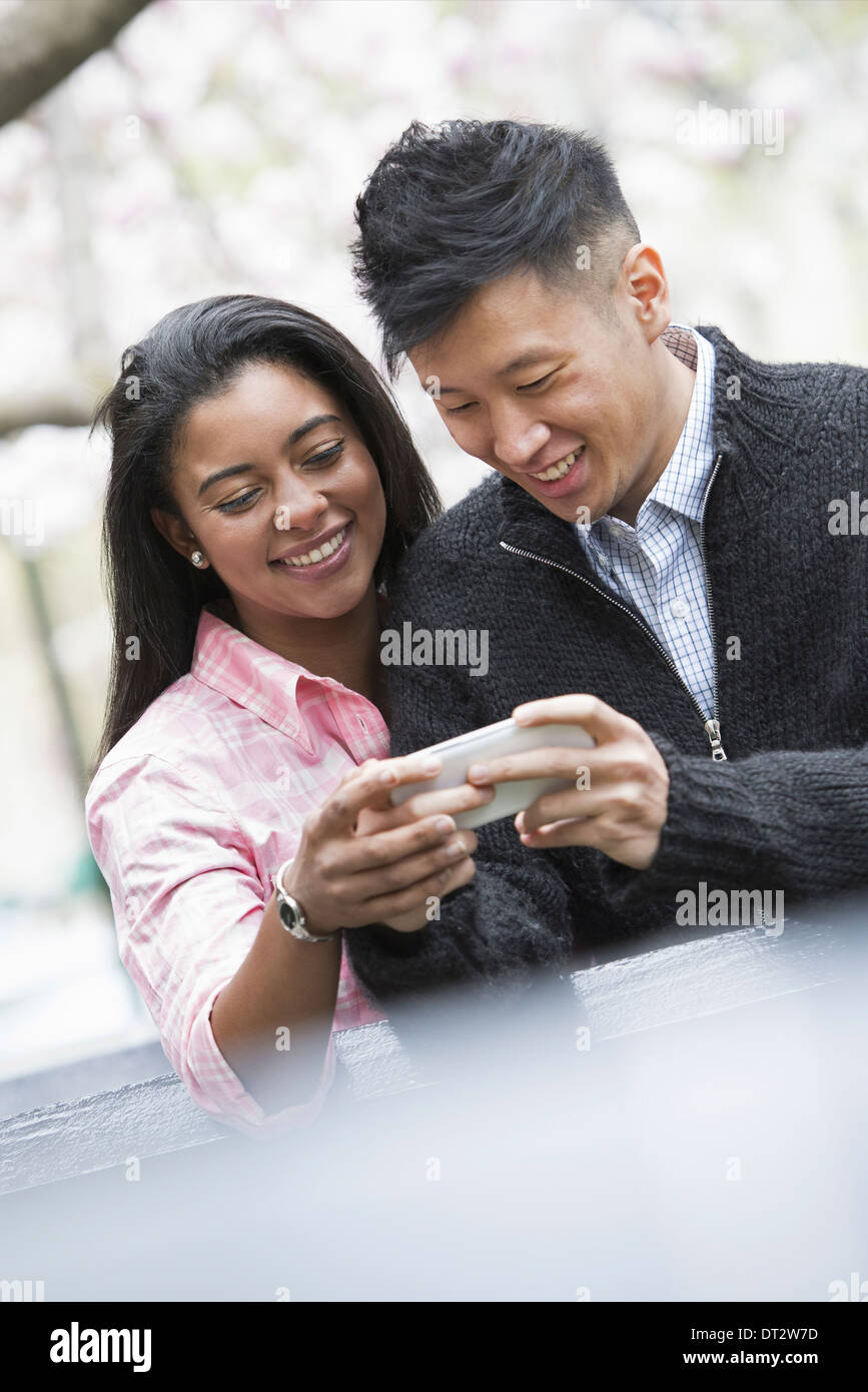 View over cityYoung people outdoors in a city park A couple side by side looking down at a smart phone - Stock Image