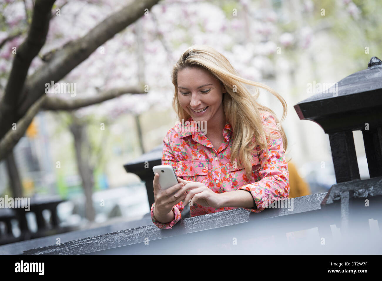 View over cityA young woman with long blonde hair sitting in a city park looking at her smart phone - Stock Image