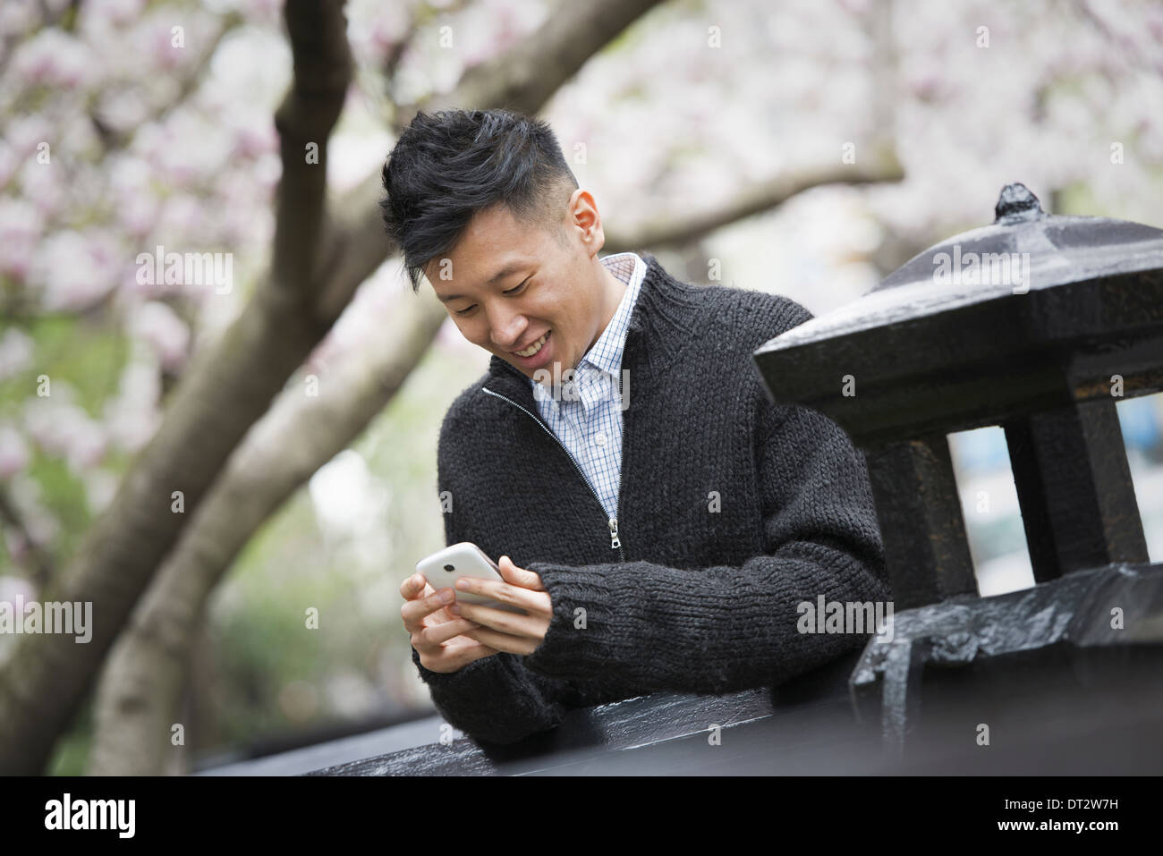 View over cityA young man outdoors in a city park Sitting on a bench Stock Photo