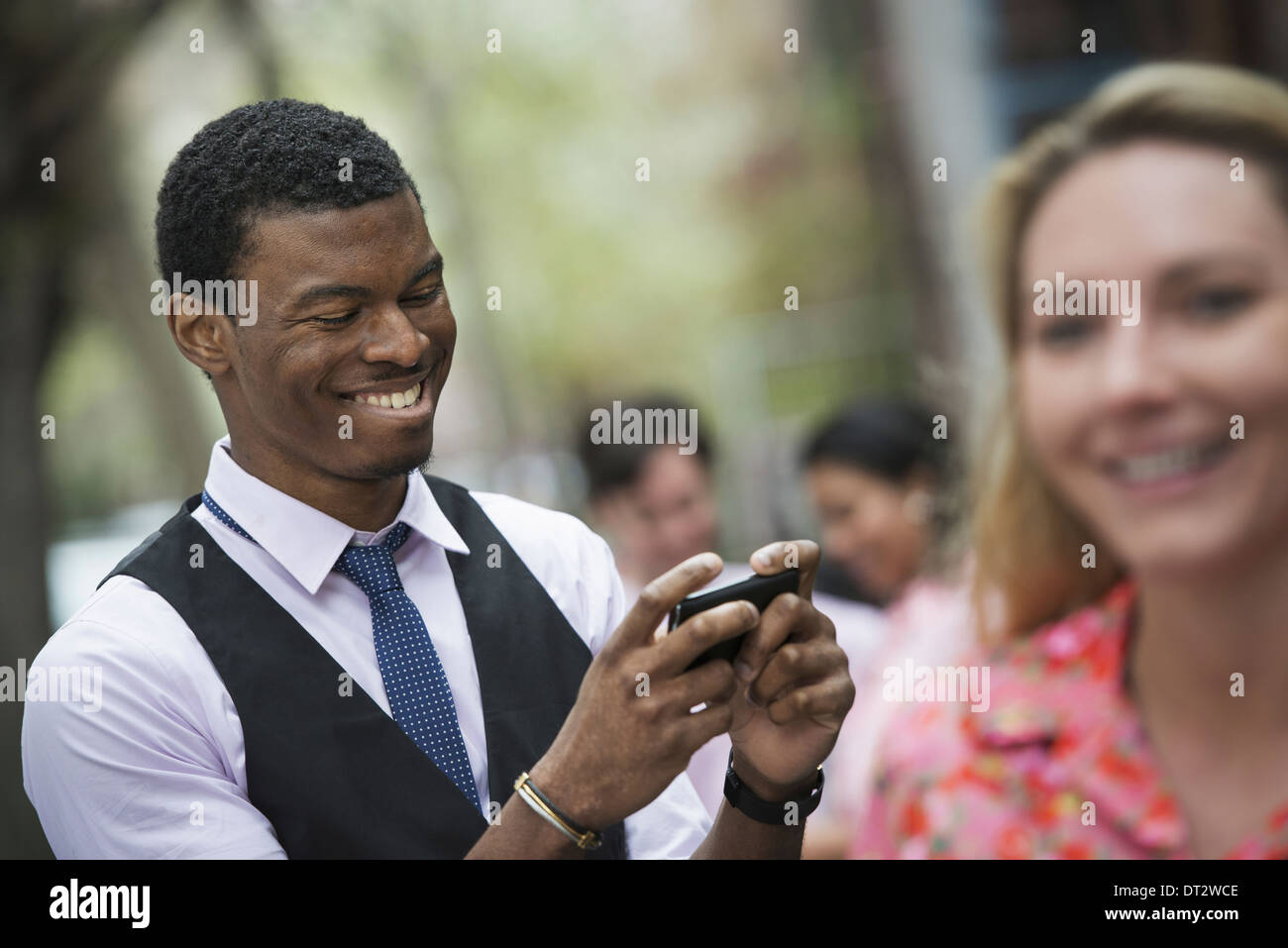 View over cityin a park A man smiling as he looks at his phone and a close of up of a woman with blonde hair - Stock Image