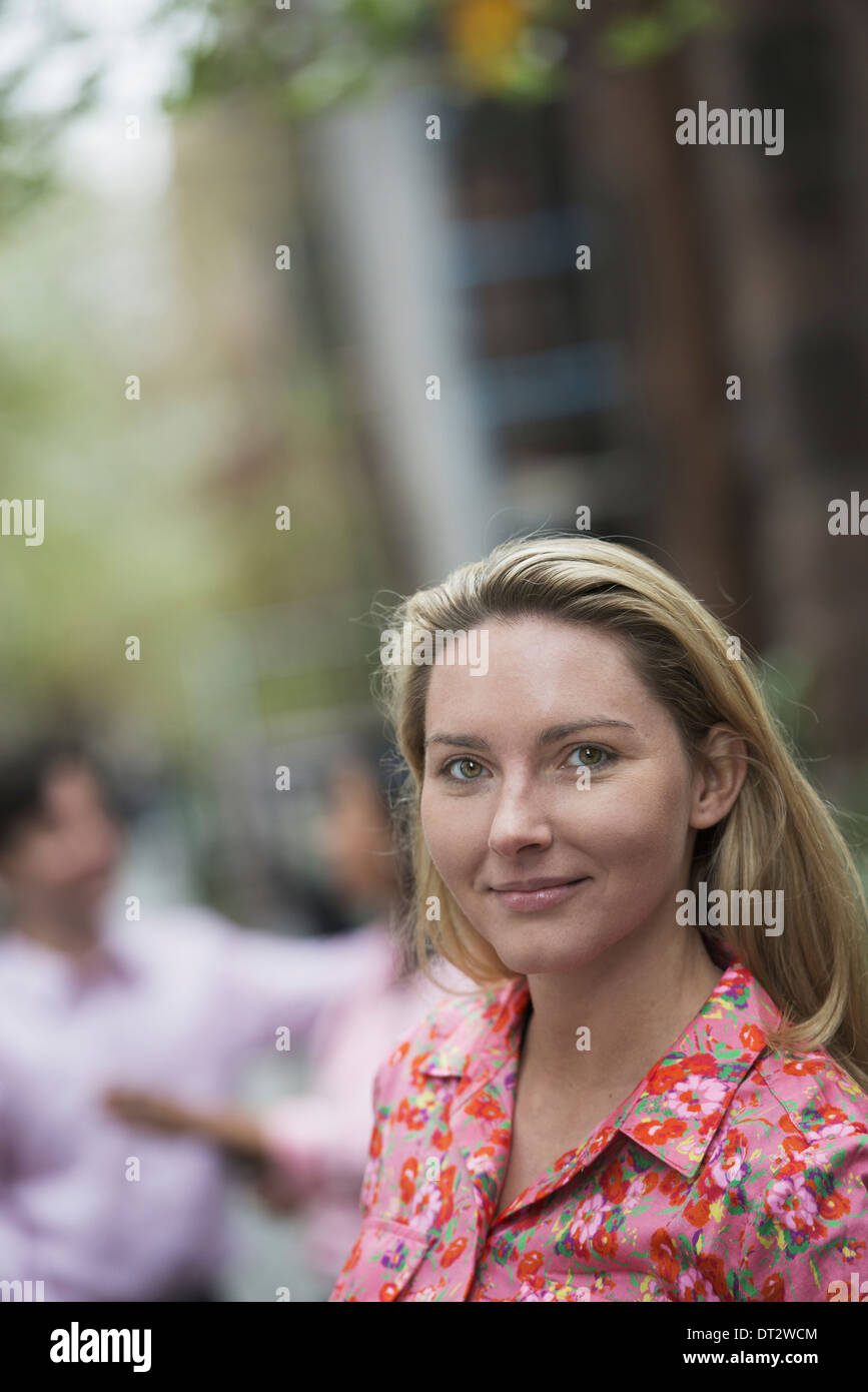 View over cityA woman with long blonde hair looking at the camera Stock Photo