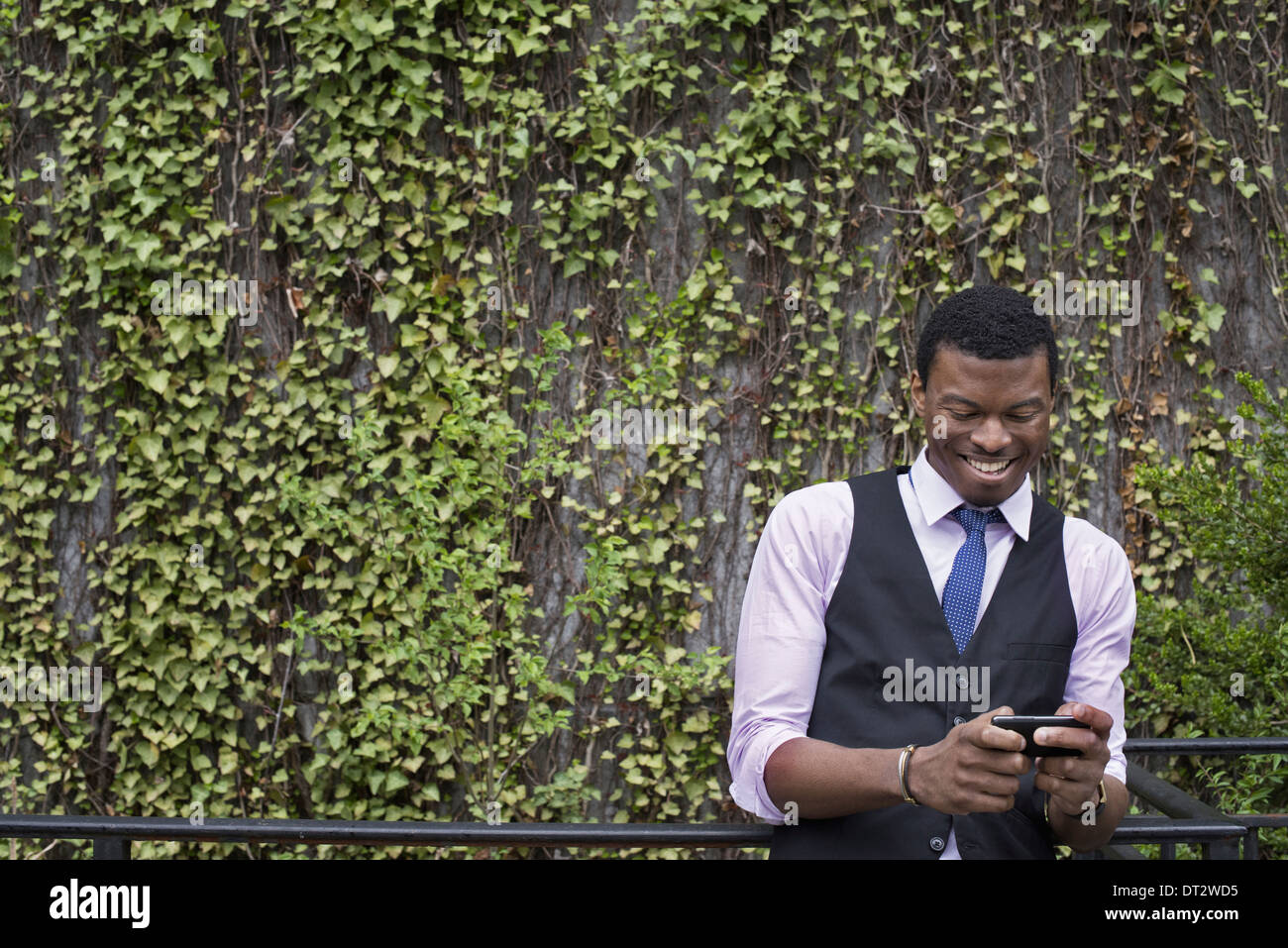 City park wall covered in climbing plants and ivy A young man in a waistcoat shirt and tie checking his phone - Stock Image