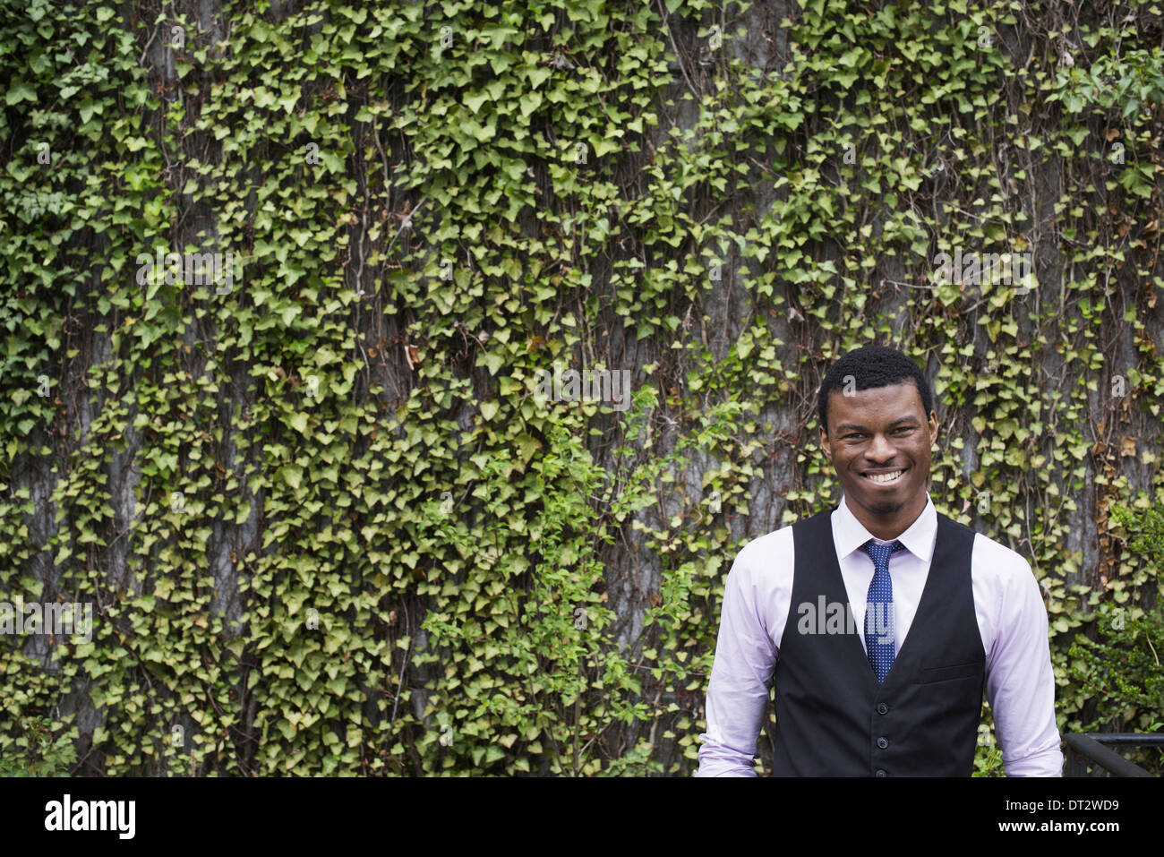 City park with a wall covered in climbing plants and ivy A young man in a waistcoat shirt and tie Looking at the camera - Stock Image