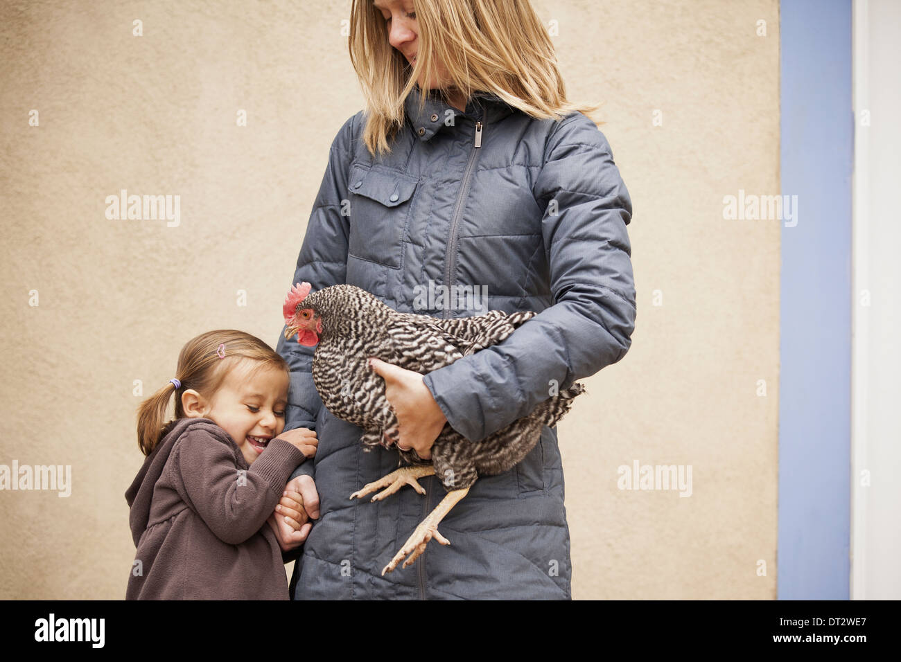 A woman holding a black and white chicken with a red coxcomb under one arm A young girl beside her holding her other Stock Photo