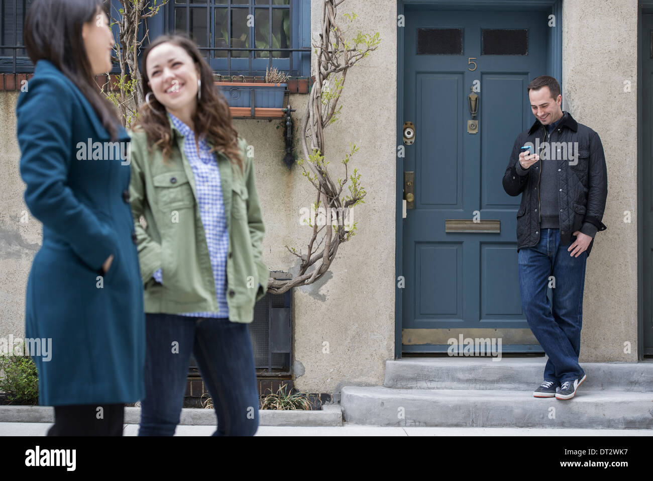 Two women talking as they walk down a street A man leaning against a house door checking his phone - Stock Image