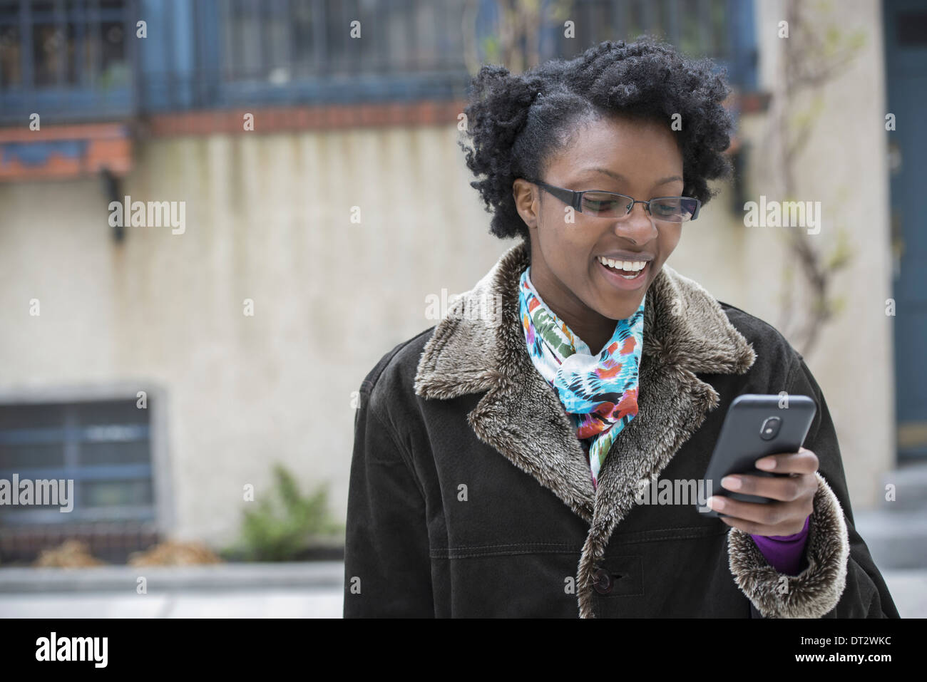 A woman wearing glasses looking at her smart phone keeping in touch while on the go - Stock Image