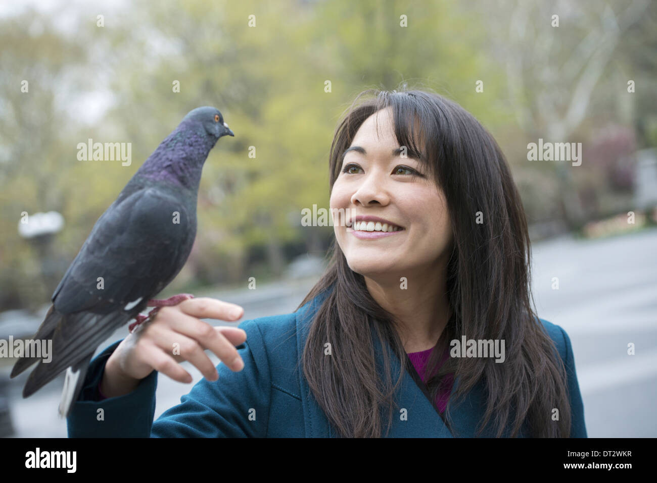 A young woman in the park with a pigeon perched on her wrist - Stock Image
